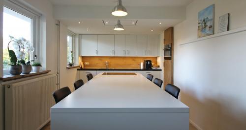 witte keuken met houten hoge kast ingebouwd